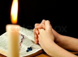 1916724-760415-open-bible-with-burning-candle-and-hands-of-praying-woman